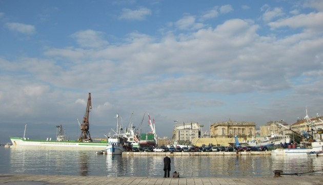 Image of Rijeka's harbour, a wooden pier reaches out to a cloudy blue sky as a long, thin boat glides slickly by.