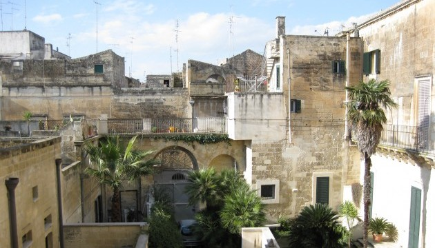 Looking out over an old baroque courtyard with sandstone buildings and palm trees.