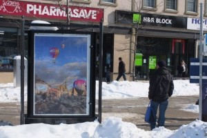 A man stands at a bus stop beside a three-faced poster stand containing a poster of a hot air balloon launch pad in downtown Guelph.