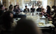 A group of people discuss around a table
