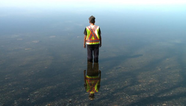A woman wearing a yellow and orange reflective safety vest stands in still water, facing away from us, her reflection glinting beneath her.