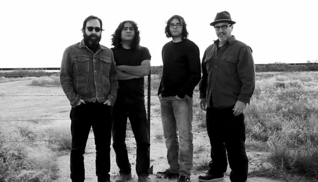 Four men stand in a desert in front of a wire fence, the horizon goes on forever. The first has a large beard, a jean jacket and dark sunglasses, the second has long hair and stands in a black t-shirt with arms crossed, the third has a slouchy sweater and running shoes and the fourth wears a trilby, square glasses, and a pointy beard.