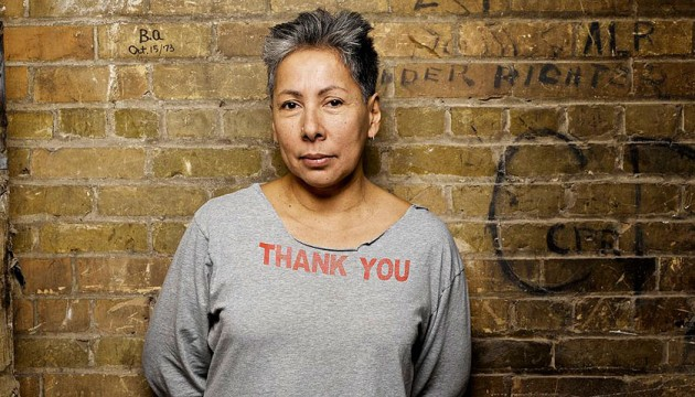 A woman with short salt-and-pepper hair wearing a grey sweatshirt reading THANK YOU in red letters stands in front of a brownstone wall.