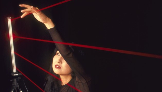 "A woman against a black background ""plucks"" red laser beams midair."