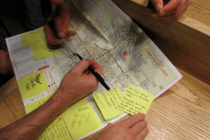 Two sets of hands annotate a map of the campus with pens and sticky notes.