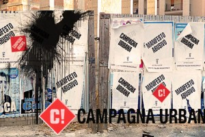 "A black spray-painted wall with wheat pasted ""Campagna Urbana"" posters all over it."