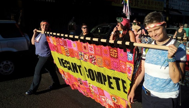 Two smiling women carry a crocheted granny square banner in neon colours in front of a parade of people.