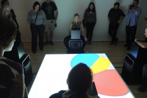 A group of people stand clustered around a projection on an inverse pyramid surface. Four video game players stand around, making music with this game.
