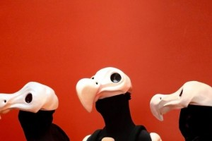 Three human-sized dodo skull costumed heads in front of a red background.