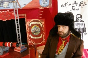 A man in a red shirt, yellow tie, vest, suit jacket, beard, and fur hat sits in a red circus-themed room.