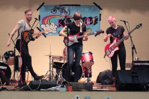 Punk band on stage, one guitarist with pink hair, one in a short pixie cut, and the other with a long goatee and moustache.