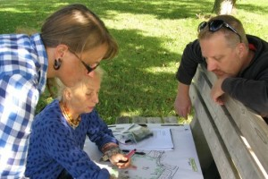 Two women and a men sit in dappled shade working on a hnad-drawn map on a park bench.