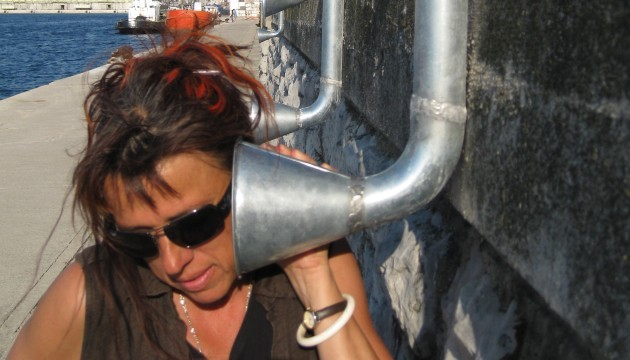 Woman puts an ear up to a flared nickel pipe.