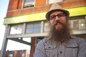 A man with a large beard, a hat and glasses in a plaid shirt stands in front of a chartreuse-bannered store.