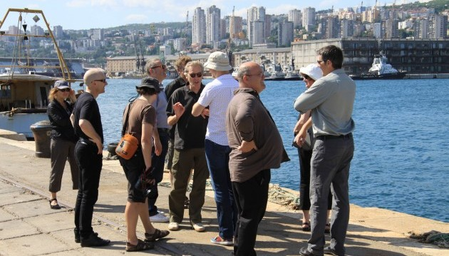 A gaggle of people stand on a pier in full sun, the water is bright blue and there are ships and the city in the background.