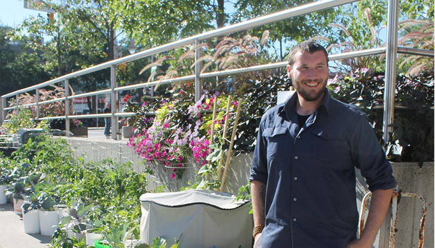 Man in a blue work shirt with a beard smiles in front of an urban container garden.