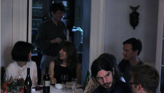 A group of people chat with each other around a table in an old victorian house.