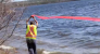 A short-haired woman in a safety vest draws a red marking ribbon over her head into the water.