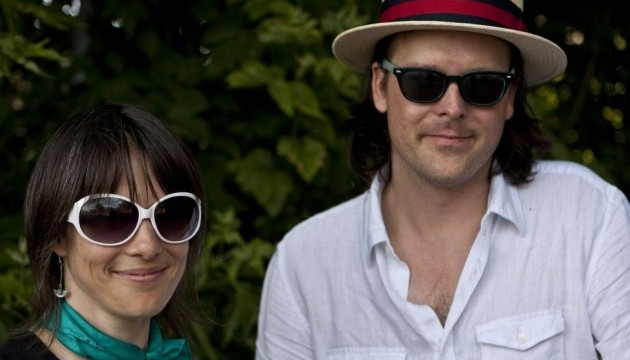A man and a woman in front of a leafy area. The woman wears white sunglasses and a bright scarf, the man wears a boater hat and a linen button-up.