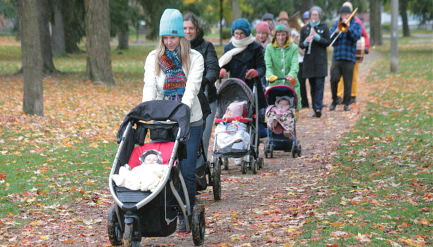 A dance parade of parents with strollers makes its way along a leaf-covered path, accompanied by musicians.