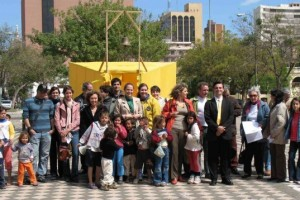 A group of 20 people stand in a courtyard in front of a pop-up yellow tent-like structure in the shape of a traditional one-room schoolhouse.