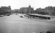 A black and white photo of a square, cars line the bottom, buildings in the back and a streetcar stops at the centre.