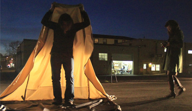 In the dusk in front of a garage door, a woman stands holding up a yellow tent over her head.