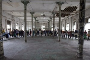 A large group of children stand side by side in bright costumes in a semi-circle around a factory, paint peeling and light filtering through old glass panes.
