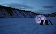 A glowing geodesic dome on a frozen field in the sunset.