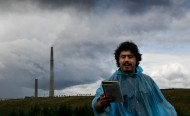 A man in a blue plastic raincoat stands reading poetry against a stormy sky, a smokestack rises up out of this wilderness in the background.