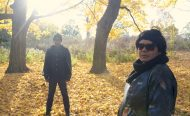 Two people standing outside. Yellow leaves cover the ground.